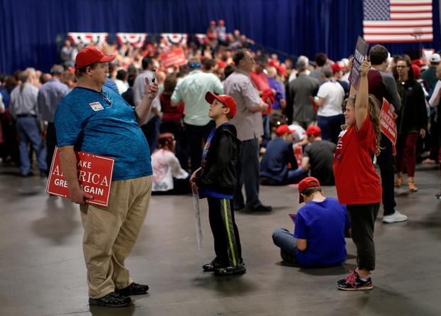 Supporter of Republican U.S. presidential nominee Donald Trump, Claude Glasgow (L) takes a picture of his daughter Moina at a Trump campaign rally in Charlotte, North Carolina, U.S., October 14, 2016. REUTERS/Mike Segar
