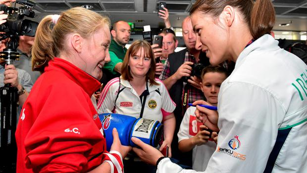 29 June 2015; Katie Taylor, Team Ireland, signs an autograph for Sophie Clancy, 12, of St. Josephs Boxing Club, Edenderry, on her return from the 2015 Baku European Games. Terminal One, Dublin Airport. Picture credit: Cody Glenn / SPORTSFILE