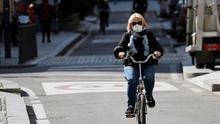 A woman wearing a protective face mask to prevent contracting the coronavirus rides her bicycle in Milan, Italy, March 4, 2020. REUTERS/Guglielmo Mangiapane