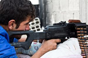 In this Wednesday, Nov. 19, 2014 photo, a young Kurdish People's Protection Units (YPG)  fighter who recently volunteered holds a position with a PKM in Kobani, Syria. (AP Photo/Jake Simkin)