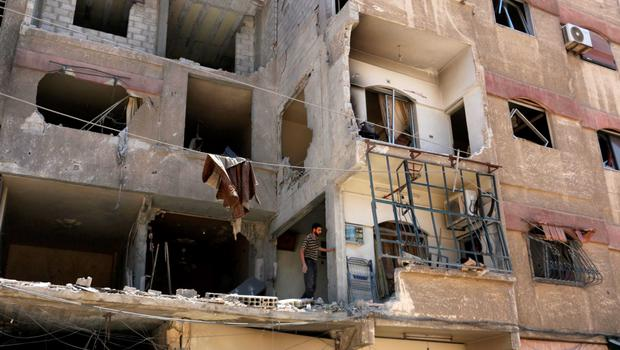 A man inspects a damaged building at a site hit by what activists said was an airstrike by forces loyal to Syria's President Bashar al-Assad, at the eastern Ghouta of Damascus June 5, 2015. REUTERS/Amer Almohibany