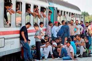 BELI MANASTIR, CROATIA - SEPTEMBER 18:  Migrants board trains a train at the train station in Beli Manastir, near Hungarian border on September 18, 2015 in Beli Manastir,Croatia. Officials are saying that they had no choice than to close eight road border crossings yesterday after more than 11,000 people entered the country since Hungary fenced off its border with Serbia earlier this week.  (Photo by Jeff J Mitchell/Getty Images)