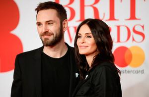 British singer Johnny McDaid (L) and partner US actress Courteney Cox pose on the red carpet on arrival for the BRIT Awards 2018 in London on February 21, 2018. / AFP PHOTO / Tolga AKMEN