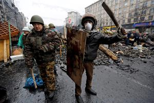 Anti-government protesters react after clashes with riot police in the Independence Square in Kiev