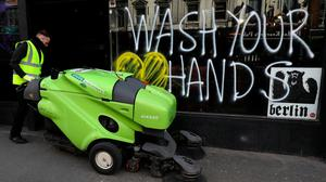 Good advice: A street cleaner passes a sign reminding people to wash their hands on the window of a bar in Dublin's city centre yesterday. Photo: Brian Lawless/PA Wire