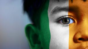 Boy's face, looking at camera, cropped view with digitally placed Ireland flag on his face. Stock picture