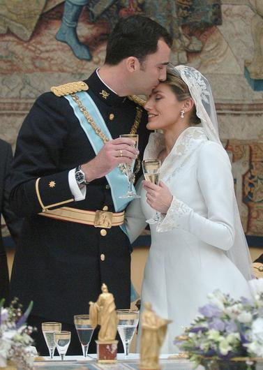 Crown Prince Felipe de Bourbon kisses his new wife Princess Letizia Ortiz during the celebratory wedding banquet at the royal palace May 22, 2004 in Madrid, Spain.  (Photo by Ballesteros-Pool/Getty Images)