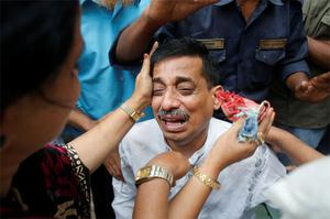 Colleagues comfort a company official as he cries after a fire at a factory belonging to Tung Hai Group, a large garment exporter, in Dhaka