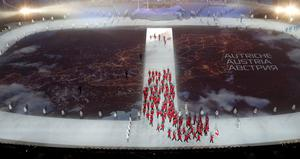 A map of Austria is projected onto the stadium floor as athletes march in during the opening ceremony of the 2014 Sochi Winter Olympics