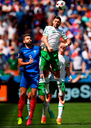 Shane Long leaps above Olivier Giroud.  Photo by Stephen McCarthy/Sportsfile
