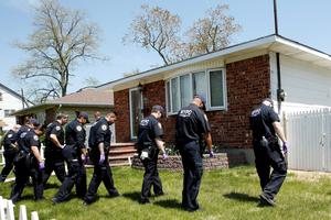 NYPD officers search house to house for the weapon used to shoot New York City plainclothes police officer Brian Moore at the Queens Village, in New York May 3, 2015. REUTERS/Eduardo Munoz