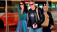 """US movie star George Clooney (C), accompanied by his wife Amal (L), arrives at Haneda airport in Tokyo on May 24, 2015. Clooney is now here for the Japanese premiere of his new film """"Tomorrowland"""","""