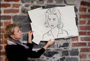 Director of the Centre Monika Sapielak  holds a stencil on envelope exhibit by artist Joseph Murphy.