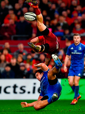 Munster's Andrew Conway is tackled in the air by James Lowe, earning the Leinster winger a red card. Photo by Ramsey Cardy/Sportsfile