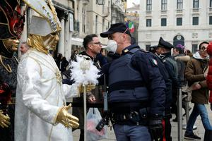 Virus fears: A police officer wearing a protective face mask stands next to carnival revellers at Venice Carnival, which has now been cancelled amid the coronavirus crisis in Italy. Photo: REUTERS