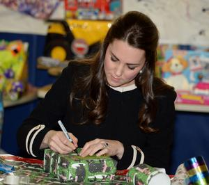The Duchess of Cambridge helps wrap Christmast presents during a visit to the Northside Center, a local child development centre in Harlem. Mark Stewart/PA Wire