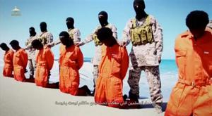Islamic State militants stand behind what are said to be Ethiopian Christians along a beach in Wilayat Barqa