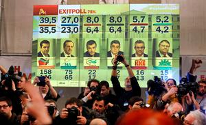 Cameramen and photographers work under a pannel displaying exit poll results in Athens, January 25, 2015.    REUTERS/Marko Djurica