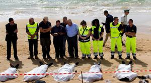 Rescue workers stand next to bodies of migrants who drowned lie on the beach in the Sicilian village of Sampieri September 30, 2013. At least 13 people on a migrant boat arriving in Sicily drowned close to the coast near the eastern city of Ragusa, apparently after trying to disembark from their stranded vessel, Italian authorities said on Monday. Officials said the boat was carrying around 250 people but there was no immediate word on where they came from.  REUTERS/Gianni Mania (ITALY - Tags: DISASTER)