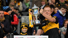 Dr Crokes's supporter Amy O'Connor lifts the Andy Merrigan Cup with captain Johnny Buckley