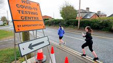 Joggers pass a sign for a testing centre in Newbridge in Co Kildare as the Covid-19 crisis continues. Photo: Niall Carson/PA Wire
