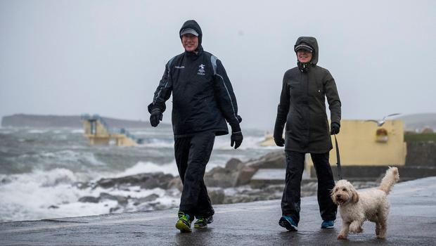 BATTEN DOWN THE HATCHES: Left, people walking the dog on Salthill promenade in Galway city. Photo: Liam McBurney