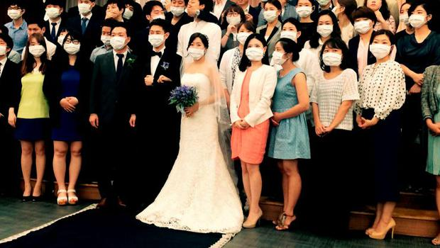 A young South Korean couple and their wedding guests  pose wearing surgical masks. The couple became an unexpected symbol of the Mers health scare sweeping the nation after another photo of them wearing masks went viral. Photo: AFP