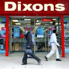 Pedestrians walk past a Dixons electrical retail shop in London - REUTERS
