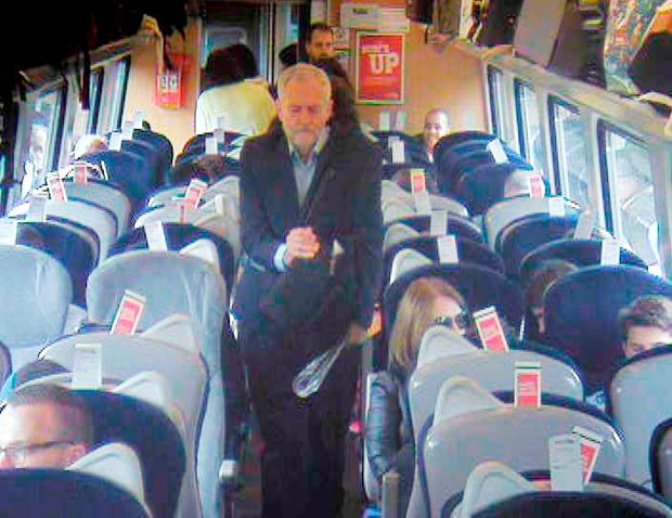 Handout CCTV footage dated 11/08/16 issued by Virgin Trains which was filmed at 11.08am, approximately 8 min after departure from King's Cross in central London, showing Labour Party leaderJeremy Corbyn, walking past several empty, unreserved seats in Coach F, after a video emerged last week which showed Mr Corbyn sitting on the floor, reading a newspaper, and saying