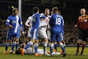Michael Dawson (C) reacts after an incident leaves Tottenham Hotspur's Belgian defender Jan Vertonghen on the ground after a clash with Dnipro's Ukrainian striker Roman Zozulya