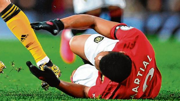 Anthony Martial falls to the ground under pressure from Romain Saiss on a frustrating day for the Manchester United man. Photo: Clive Mason/Getty Images