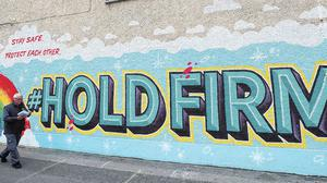 Time to deliver: A postman walks past a Dublin mural inspired by the HSE 'Hold Firm' campaign. Photo: Brian Lawless/PA
