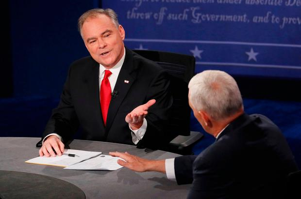 Tim Kaine (L) and Mike Pence discuss an issue during their vice presidential debate at Longwood University in Farmville, Virginia. Photo: Reuters