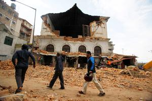People walk past a building that was damaged in an earthquake in Kathmandu, Nepal, Saturday, April 25, 2015. A strong magnitude-7.9 earthquake shook Nepal's capital and the densely populated Kathmandu Valley before noon Saturday, causing extensive damage with toppled walls and collapsed buildings, officials said. (AP Photo/ Niranjan Shrestha)