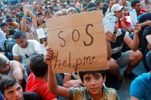 """A child holds a self-made placard reading """"SOS help me"""" outside the railways station in Budapest, Hungary. Photo: Reuters"""