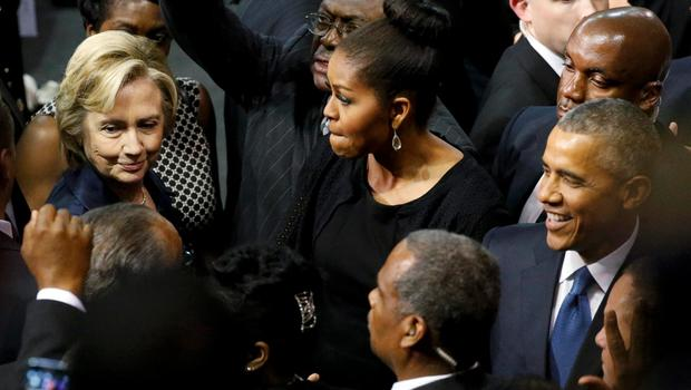 U.S. Democratic presidential candidate Hillary Clinton (L) talks with first lady Michelle Obama and President Barack Obama after the conclusion of funeral services for Rev. Clementa Pinckney in Charleston, South Carolina June 26, 2015. Pinckney was one of nine victims of a mass shooting at the Emanuel African Methodist Episcopal Church.   REUTERS/Jonathan Ernst