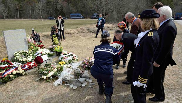 French Interior Minister Bernard Cazeneuve (2ndL) is helped by a gendarme as he places a wreath by a stele in memory of the victims of the Germanwings Airbus A320 crash, on April 3, 2015  in the village of Le Vernet, French Alps.   REUTERS/Lionel Bonaventure/Pool