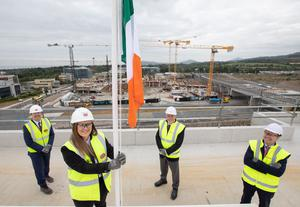 Hannah Ward, a health and safety officer at Sisk in Cherrywood raising the Irish tricolour watched (L to R) by Donal McCarthy, COO (Ireland and Europe) John Sisk & Son, Brian Moran, Senior MD, Hines and Gary Corrigan, MD at Hines.