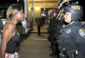 A woman confronts a female police officer in Ferguson on Tuesday. REUTERS/Elijah Nouvelage
