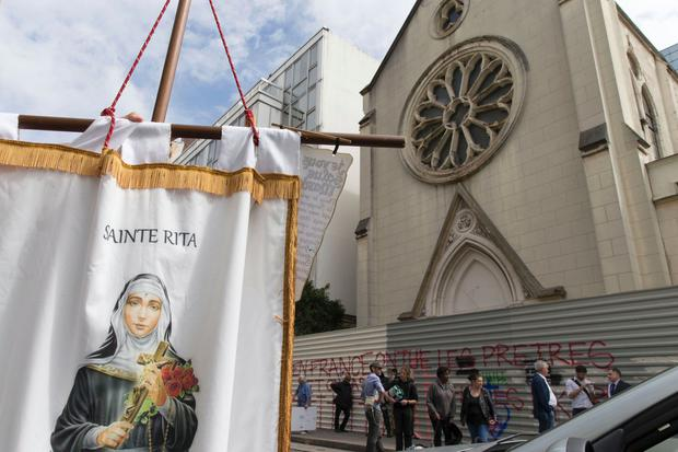 A person holds a banner picturing Sainte-Rita as other stand in front of barriers blocking the access to the sainte-Rita church in Paris with an inscription on it which translates as In France, priests are killed and churchs are demolished
