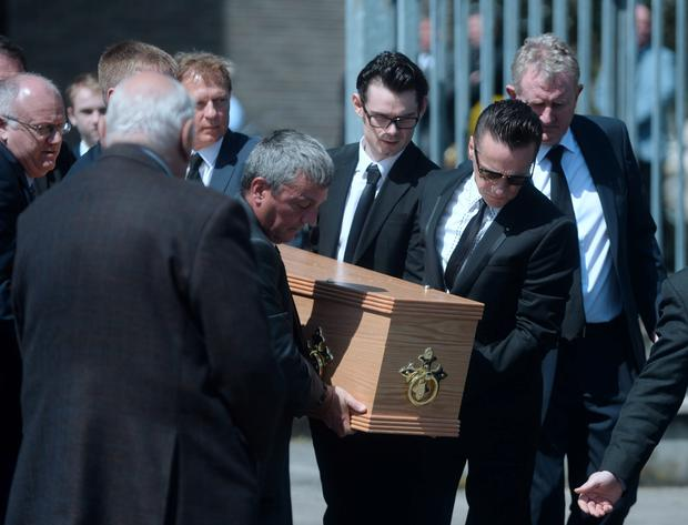 Larry Mullen Jr. carries the coffin of his late father Larry Mullen Sr. from the church following the funeral