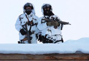 Two armed Swiss police officers stand on a roof top during the 'World Economic Forum' in Davos, Switzerland, Tuesday, Jan. 17, 2017. Business and world leaders are gathering for the annual meeting 'World Economic Forum ' in Davos. (AP Photo/Michel Euler)