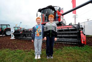 Ben, 8, and brother George Guiney, 8, from Brosna, Co. Kerry, pictured with a Combine Harvester.  National Ploughing Championships 2014. Ratheniska, Stradbally, Co. Laois. Picture: Caroline Quinn