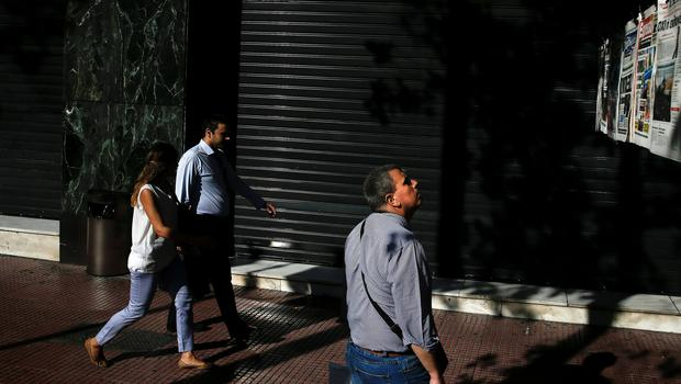 A man (R) reads newspaper headlines in Athens, Greece June 30, 2015. The head of the European Commission made a last-minute offer to try to persuade Greek Prime Minister Alexis Tsipras to accept a bailout deal he has rejected before a referendum on Sunday which EU partners say will be a choice of whether to stay in the euro. REUTERS/Alkis Konstantinidis