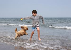 Making a splash: Harry McKeever (10) from Portmarnock runs in the shallow sea water with his dog George at Portmarnock Beach. PHOTO: FRANK McGRATH