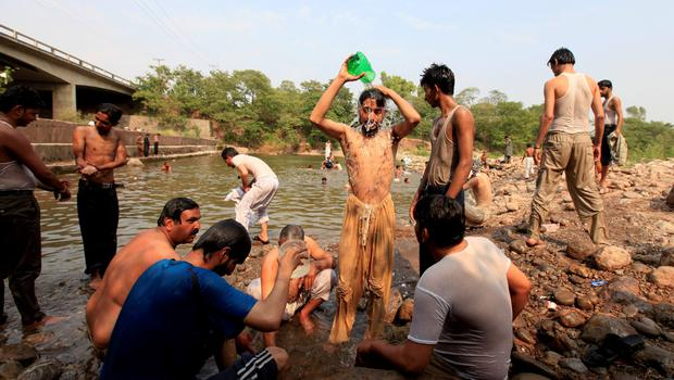 Men cool off at a stream during  a hot day in Islamabad, Pakistan, June 23, 2015. A devastating heat wave has killed more than 400 people in Pakistan's southern city of Karachi over the past three days, health officials said on Tuesday, as paramilitaries set up emergency medical camps in the streets.  REUTERS/Faisal Mahmood