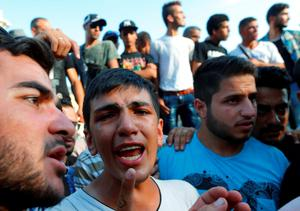 Amam, a17-year-old refugee from the Syrian town of Latakia has tears in his eyes as he cries for his sister and mother who were detained by Hungarian police outside the railways station in Budapest, Hungary. Photo: Reuters