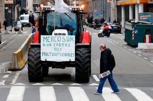 """A sign reading """"Mercosur = a gift to multinationals"""" is pictured on a tractor during a protest by Belgian farmers outside a meeting of European Union agriculture ministers in Brussels on January 29. REUTERS/Francois Lenoir"""