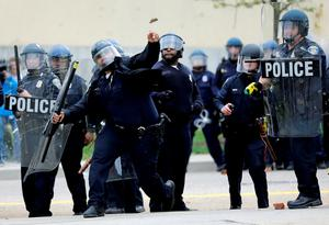 A police officer throws an object at protestors following the funeral of Freddie Gray in Baltimore. Photo: AP