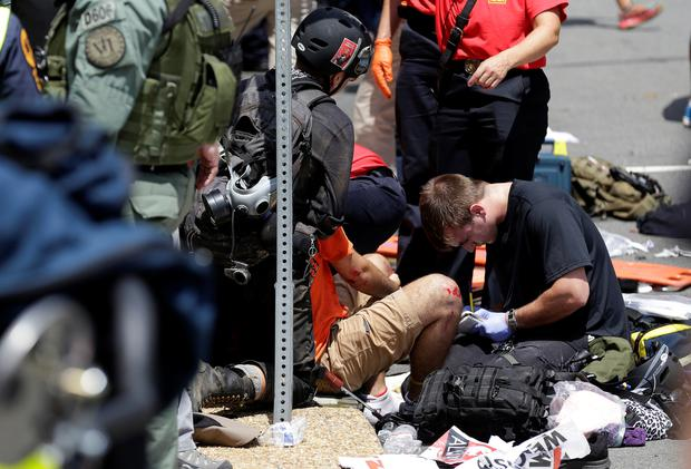 Rescue workers assist people who were injured when a car drove through a group of counter protestors at the